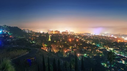 Fototapete - Zoom in Hollywood skyline fog moving across cityscape at night. Los Angeles. 4K