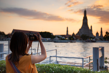 A young girl tourist is taking the picture of pagoda at temple of dawn or Wat Arun with having Chao Phraya River in the front at the sunset moment