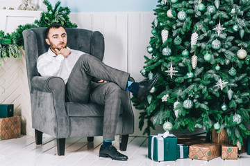 A man sitting in a chair near the Christmas tree
