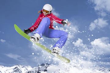Snowboarderin springt auf ihrem Snowboard durch die Luft