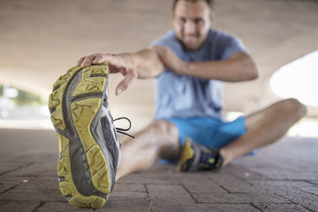 Sportive man sitting and stretching