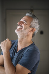 Portrait of laughing mature man at home