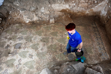 A worker leaves after cleaning an ancient mosaic floor, decorated with birds, leaves and pomegranates, revealed during an Israeli Antiquities Authority excavation of a Christian pilgrimage center which is around 1,500 years old, in Beit Shemesh