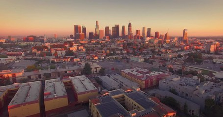 Fototapete - Aerial view downtown Los Angeles cityscape skyline sunset camera flying backward