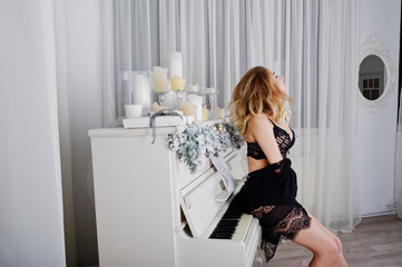 Sexy blonde model in black lingerie and high heels against white piano with candles christmas decorations.