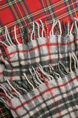 Woolen warm checkered scarf on a red background