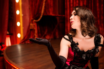 Elegant dancer in moulin rouge style sends an air kiss from the stage