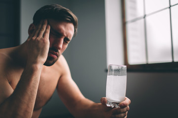 Sad guy suffering from hangover in morning. Naked bearded dark-hair sleepy young man holding a glass of water.
