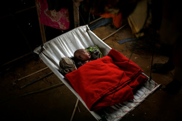 A Rohingya refugee baby girl sleeps inside her family's temporary shelter at the Balukhali refugee camp near Cox's Bazar