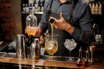 Barman pouring a portion of syrup into the large cocktail glass