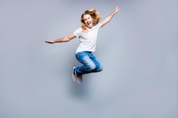 Handsome carefree young delightful guy with long blonde hair is screaming and jumping up, isolated on grey background