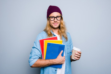 Portrait of attractive, nice, cute guy in cap holding three colorful copy books and mug of coffee standing over grey background