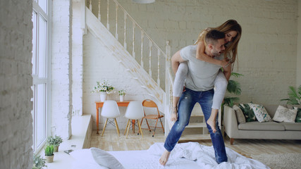 Young beautiful and loving couple dancing while having piggyback ride on bed in the morning at home