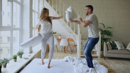 Young happy and loving couple having pillow fight in bed at home