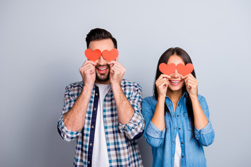 Love story of sweet, cheerful, positive, smiling couple in shirts holding small red paper hearts on eyes place over grey background