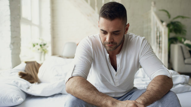 Upset young man sitting in bed suffer of problems while his girlfriend sleep in bedroom