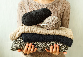 Picture of cozy knitted woolen sweaters in woman's hands