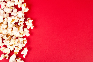 Popcorn on red background with empty space, top view