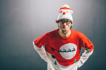 Moody man in funny christmas clothes sticking out his tongue