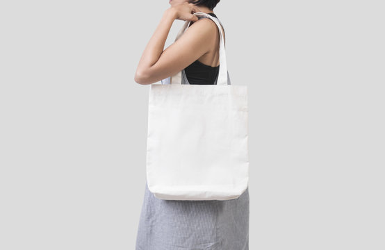 Girl is holding bag canvas fabric for mockup blank template isolated on gray background.