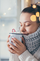 Close up of woman drinking hot chocolate next to the window. Winter theme