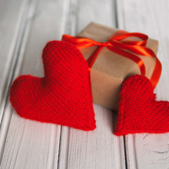Closeup of two red hearts and Valentine gift to