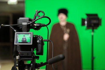 The actor starred in the interior on a green background. The chroma key. Filming equipment.