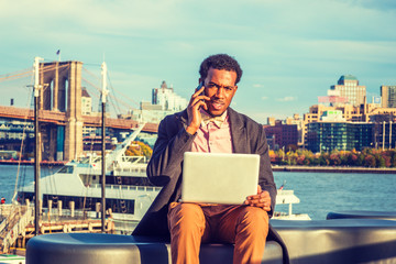 African American Businessman traveling, working in New York, wearing woolen overcoat, pink shirt, bow tie, sitting on bench at harbor, working on laptop computer, talking on phone in same time..