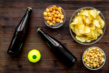 Snacks for watching sport matches and games on TV. Crisps, popcorn, rusks near drink and ball on dark wooden background top view