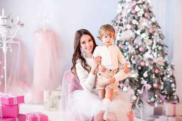Smiling woman holding baby boy over Christmas lights. Looking at camera. Winter season.