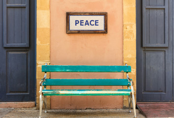 Word peace framed above an old wooden bench on a column. Close up view.