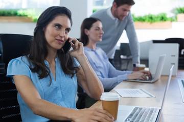 Female executive talking on phone while holding coffee mug