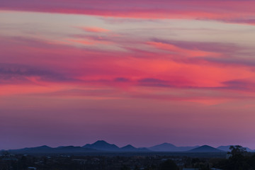 super pink horizontal clouds light up over a small town in the southwest Wall mural