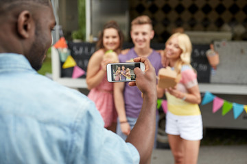 man taking picture of friends eating at food truck
