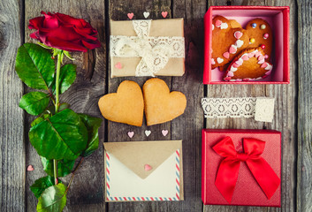 Festive composition with homemade cookies in shape of heart, rose flower, gift box. card with envelope, vintage ribbon. Gift for lover on Valentine's day. VIntage card. Selective focus, top view.