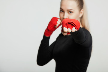 Female boxer makes a fight with a shadow, white background with space for text. Strong and confident, she will be a champion.