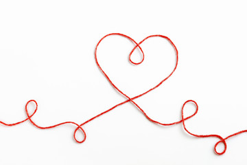 Red woolen thread in the shape of heart on white background