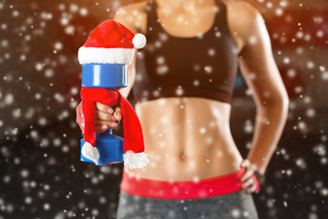 Slim, bodybuilder girl, lifts heavy dumbbell while training in the gym. Sports and New Year's concept, fat burning and a healthy lifestyle.