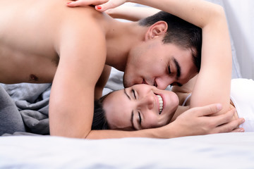 Newlyweds gently kissing in bed in the early morning, good morning.