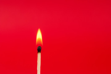 Matchstick burned on red background