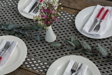 Plates with napkin, fork, butter knife and flower arranged on