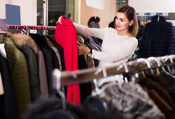 woman choosing red woolen coat in women's cloths store