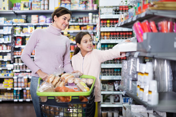 Woman with girl looking for food in supermarket