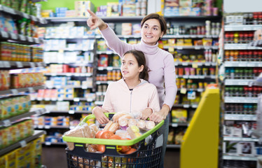 Glad woman and daughter with shopping cart