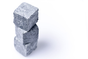 Three grey stone for whiskey stand on top of one another on a white background.
