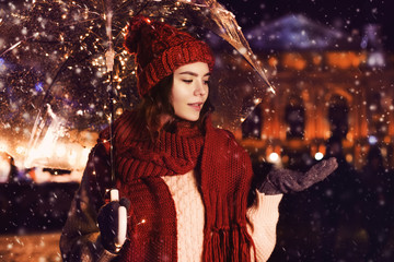 Outdoor night portrait of young beautiful happy girl catching snow, posing in street of european city. Model wearing knitted red beanie hat, scarf, sweater, gloves, holding umbrella with garland.