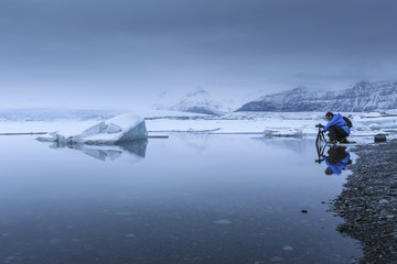 Photographer near still glacial waters, Iceland