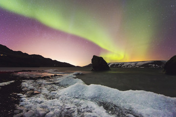 Kleifarvatn frozen lakeshore, Aurora Borealis and glow of nearby Reykjavik lights, Iceland