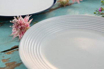 Empty plate with flower on wooden table