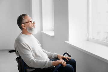 Senior man in wheelchair at empty room